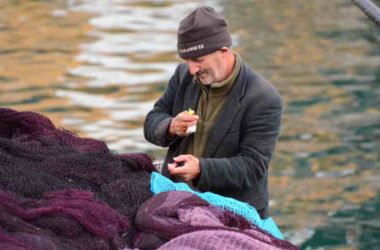 A fisherman at Anadolu Kavagi works on his net.