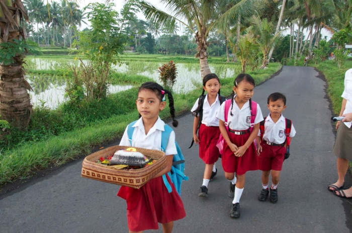 Girls carrying the early morning offerings to school.