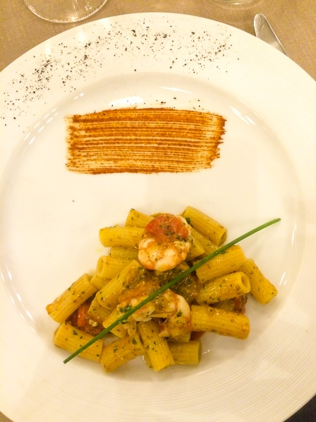 Portion of shrimp with penne, adorned with chive, smoked paprika, and black salt