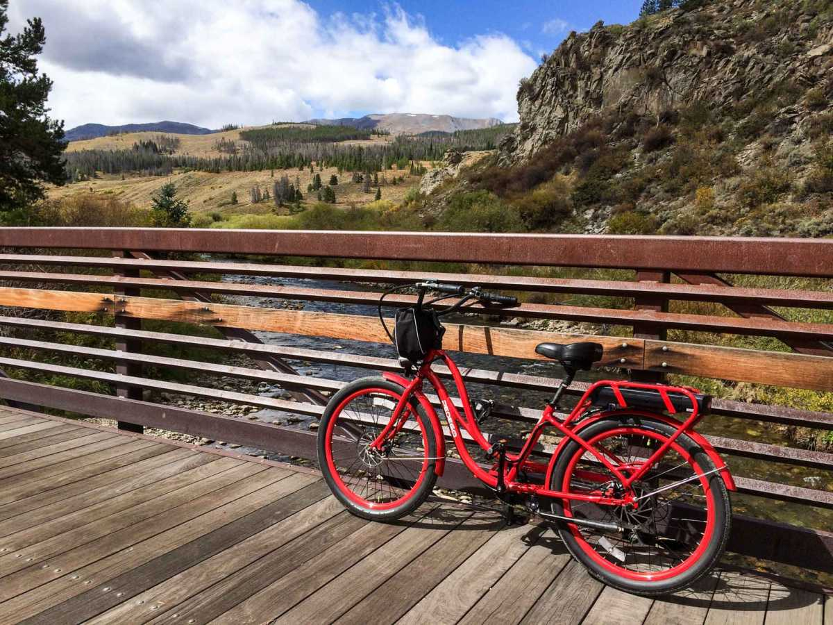A pedal-assist bike is the way to go–and return. Parked here on a bridge over the reclaimed Blue River north of Breckenridge.