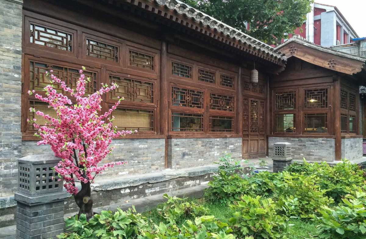 A garden and preserved wooden window screens at the Shijia Hutong Museum offer relief from the rows of gray buildings.